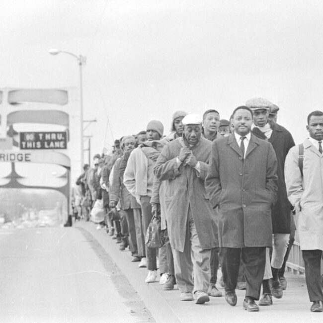 Signature image for sharing: John Lewis and many other civil rights protestors at the Edmund Pettis bridge at Selma, 1965. Black and White news photo in pub domain.