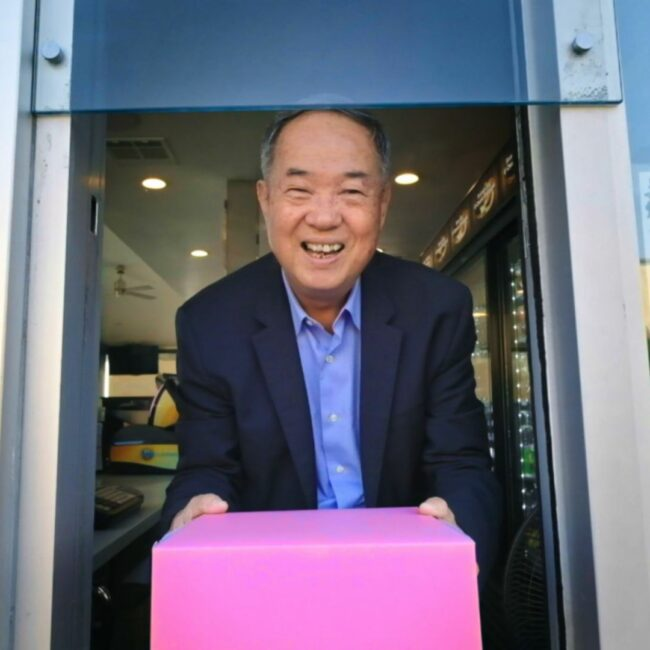 Ted Ngoy holds his famous pink pastry box, in The Donut King