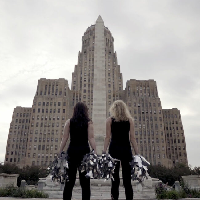 two women cheerleaders from a Woman's Work pose together as cheerleaders in front of courthouse