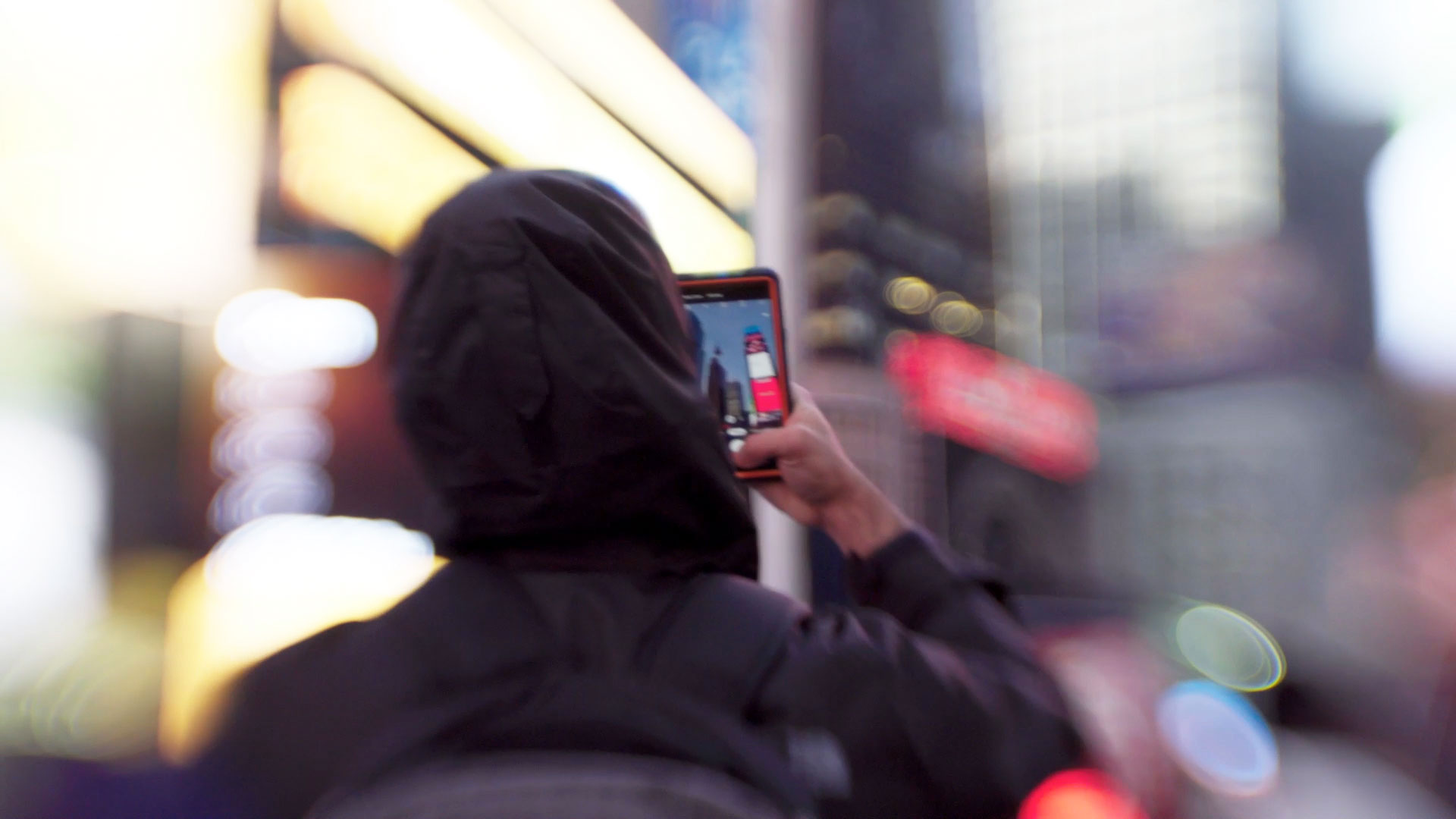 A person scanning their face on smartphone on city street, in a Still from Coded Bias, directed by Shalini Kantayya