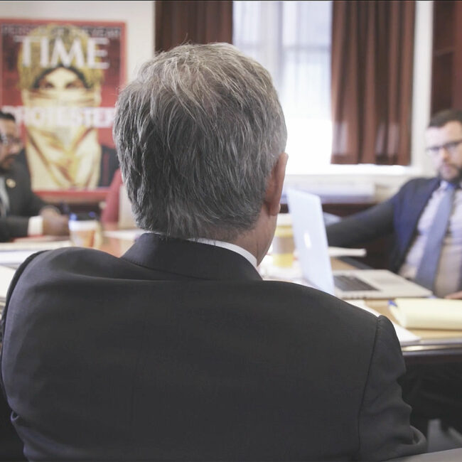 The back of Larry Krasner in Philly D.A. as he meets with his team