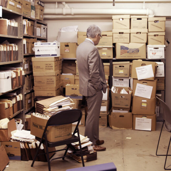 Larry Krasner looks over a ton of file boxes from way back, in Philly D.A.