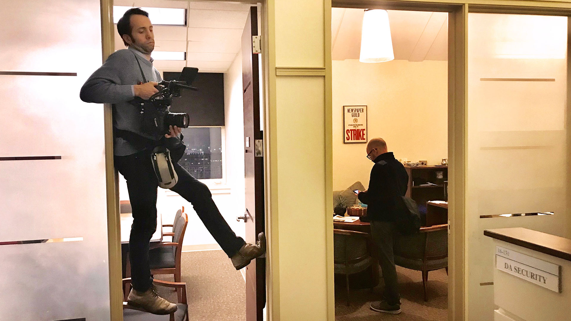 """Yoni Brook precariously, filming of """"Philly D.A."""" awkwardly positioned in doorway with camera"""