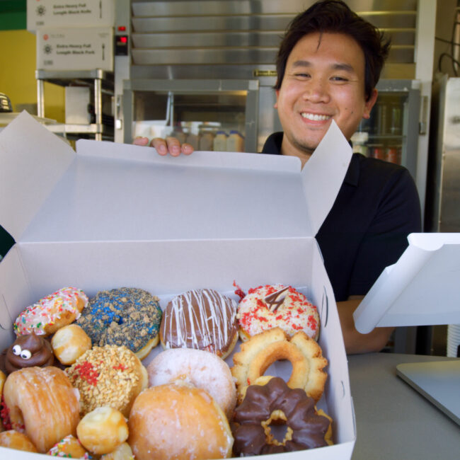 A smiling Cambodian American donut clerk offers up a box full of donuts in Southern California