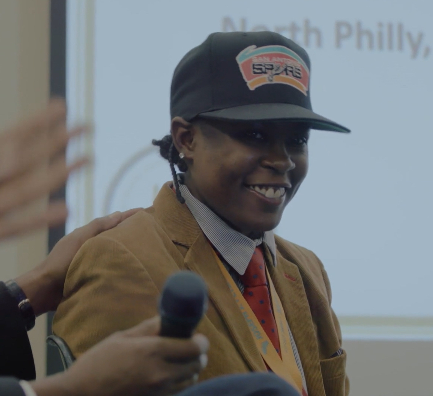 LaTonya Myers, in a San Antonio Spurs hat, celebrates a job offer, in Philly D.A.