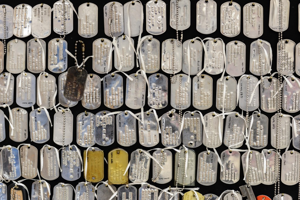 A collection of dog tags left at the Vietnam wall are displayed at the center. Photo by Ariel Min/PBS NewsHour