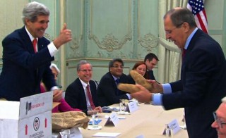 Secretary of State John Kerry hands out potatos
