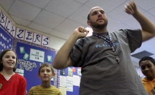 Tom O'Neill, the Playworks coach at Fox Hill Elementary School in suburban Indianapolis, Indiana shares a new game with his students at indoor resource.  Photo by Mike Fritz/PBS NewsHour