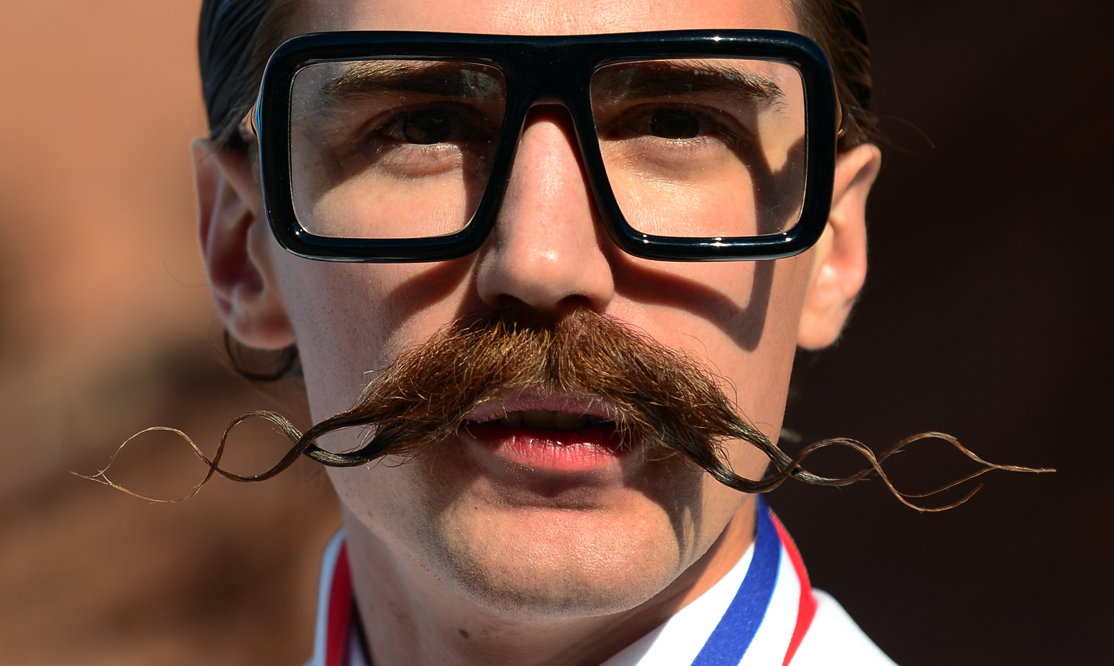 A contestant sports an elaborate mustache at the  National Beard and Moustache Championships in Las Vegas in 2012. Recent trends favoring more facial hair on men have shaved the bottom line for Procter & Gamble.