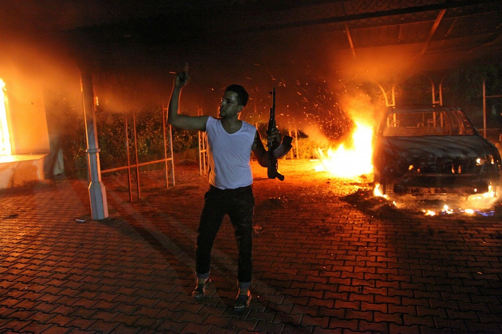 An armed man waves his rifle as buildings and cars are engulfed in flames after being set on fire inside the US consulate compound in Benghazi late on September 11, 2012. An armed mob protesting over a film they said offended Islam, attacked the US consulate in Benghazi and set fire to the building, killing one American, witnesses and officials said. Photo by STR/AFP/GettyImages