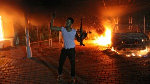 An armed man waves his rifle as buildings and cars are engulfed in flames after being set on fire inside the US consulate compound in Benghazi late on September 11, 2012. The capture of an alleged leader of the deadly 2012 attacks on Americans in Benghazi, Libya, gave U.S. officials a rare moment of good news. Now, they are preparing to try the captured Libyan in the U.S. court system. File photo from the scene of the explosion by STR/AFP/GettyImages