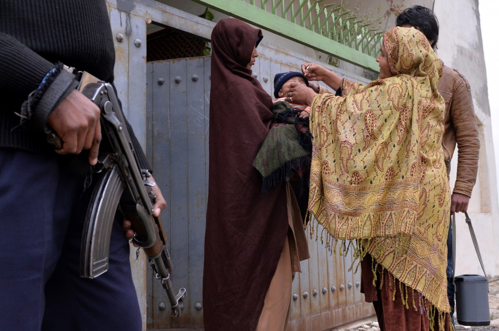 A Pakistani policeman stands guard as a health worker administers polio vaccine drops to a child during a door-to-door polio immunization campaign on the outskirts of Islamabad on January 22, 2014. Photo by Aamir Qureshi/AFP/Getty Images