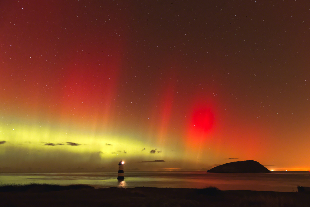 Spectacular colors of the Northern Lights look like fire in the sky over the water near Black Point, Wales. Photo by Flickr user Adrian Kingsley-Hughes.