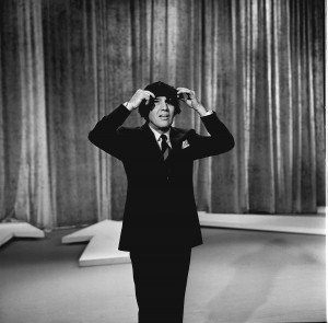 "Ed Sullivan wears a ""Beatles"" wig on the stage of his variety show during The Beatles first ever live U.S. television performance. Photo by CBS/Getty Images"