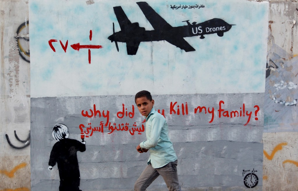 "A Yemeni boy walks past a mural reading "" Why did you kill my family"" on Dec. 13, 2013, in the capital Sanaa. A new report says that a drone strike on a wedding in southern Yemen a day earlier may have killed up to a dozen civilians. Photo by Mohammed Huwais/AFP/Getty Images"