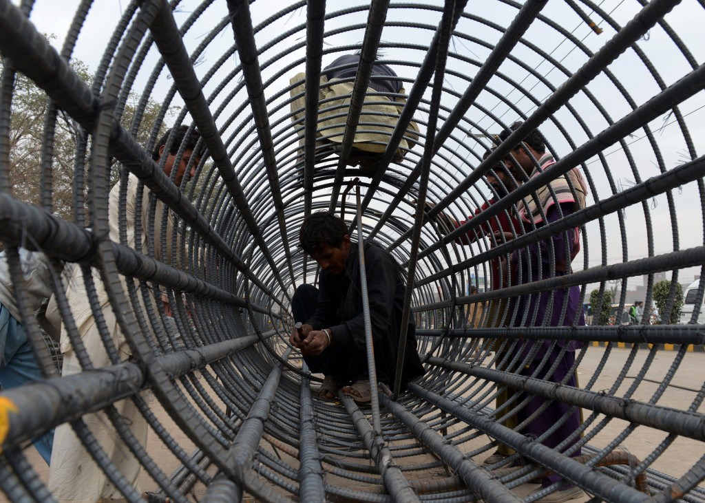 Pakistani labourers prepare a steel pillar at a construction site in Lahore on January 21, 2014. Pakistan's central bank estimated economic growth for the current fiscal year of up to four percent, surpassing forecasts by international agencies. AFP PHOTO/Arif ALI (Photo credit should read Arif Ali/AFP/Getty Images)