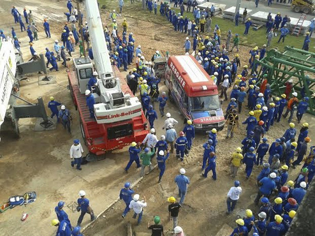 Workers surround an ambulance as a 55-year-old Portuguese worker is rushed to hospital after being seriously injured when a piece of iron fell on his head when disassembling a crane, at the Amazonia Arena in Manaus, northern Brazil, on February 7, 2014. The 42,000 arena, which will host four matches of the Brazil 2014 FIFA World Cup, has been beset by problems during construction including the deaths of two workers.  Credit: AFP/Getty Images