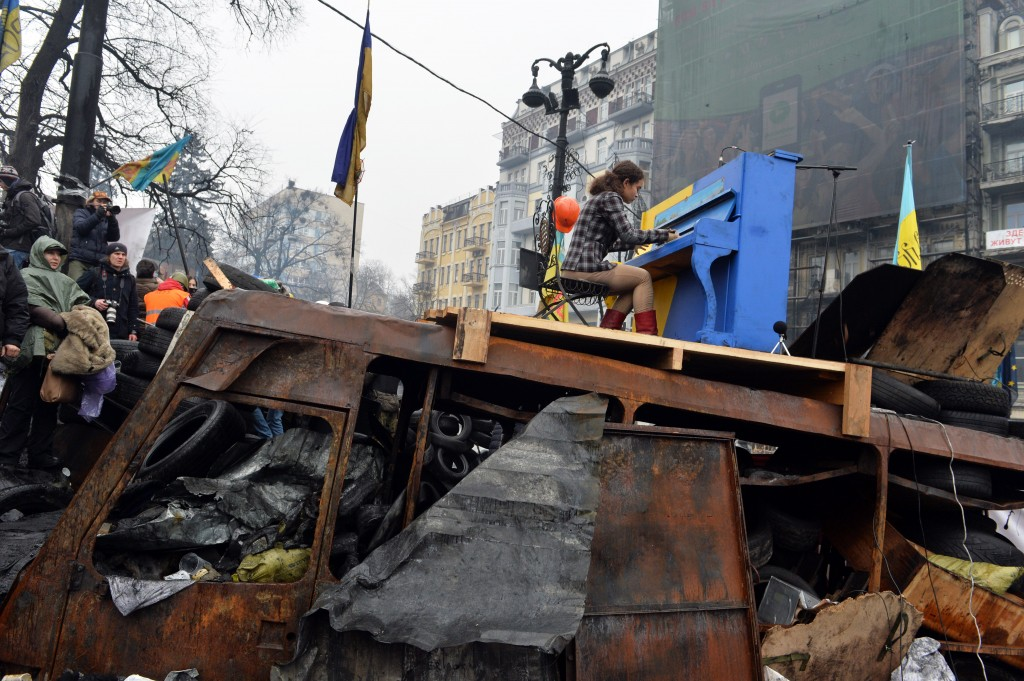 A Ukrainian artist plays the piano set on the anti-government opposition barricade in Kiev during a concert organized for the activists and for the policemen on February 10, 2014. Photo by AFP/Sergei Supinksy