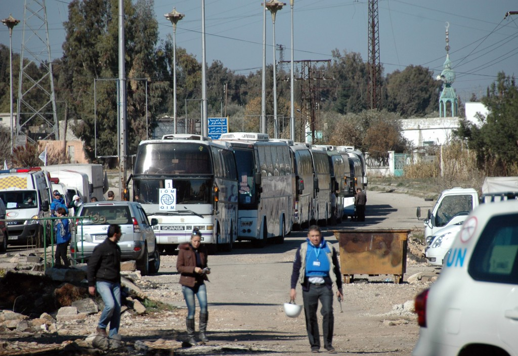 Buses carrying Syrian civilians who were evacuated from rebel-controlled districts that were besieged by the army, arrive at a government-ruled area, in the central Syrian city of Homs, on February 12, 2014.  Photo By STR/AFP/Getty Images