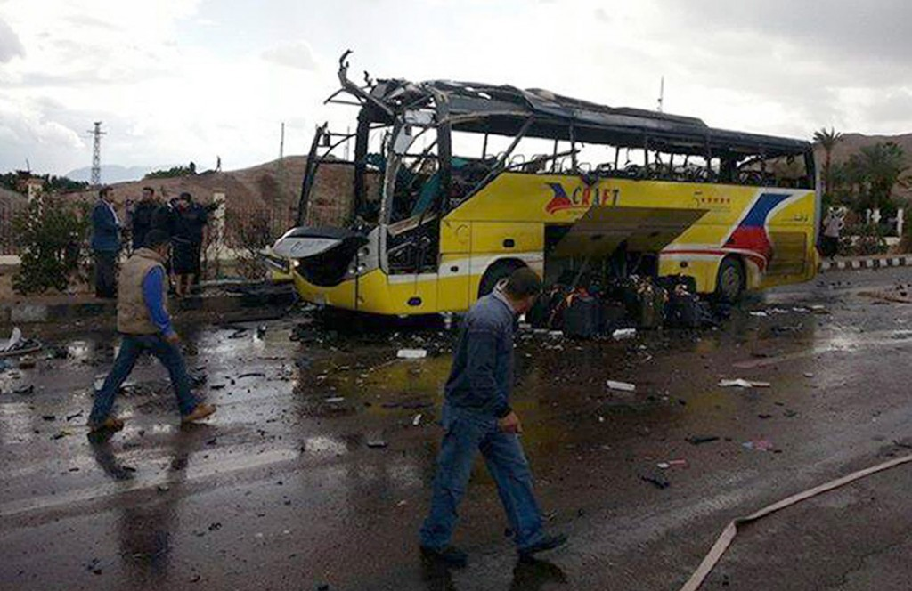 A picture taken on February 16, 2014, shows flames rising from the wreckage of a tourist bus at the site of a bomb explosion in the Egyptian south Sinai resort town of Taba. A bomb tore through a bus carrying South Korean tourists near an Egyptian border crossing with Israel, killing at least four people and wounding 13, officials said. AFP PHOTO / STR (Photo credit should read STR/AFP/Getty Images)