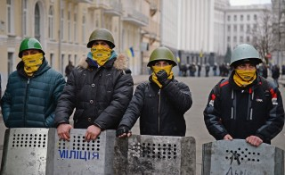 Anti-government protesters stand outside the presidential offices after Yanukovych and his administration left Kiev on Saturday.