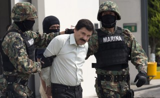 "Drug trafficker Joaquin ""El Chapo"" Guzman is escorted to a helicopter by Mexican security forces on Saturday. Photo by Susana Gonzalez/Bloomberg via Getty Images"