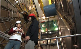 "Fabiola Gianotti and David Kaplan talk at the Large Hadron Collider, where the Higgs particle was discovered in 2012. Photo courtesy ""Particle Fever"" Bond/360"