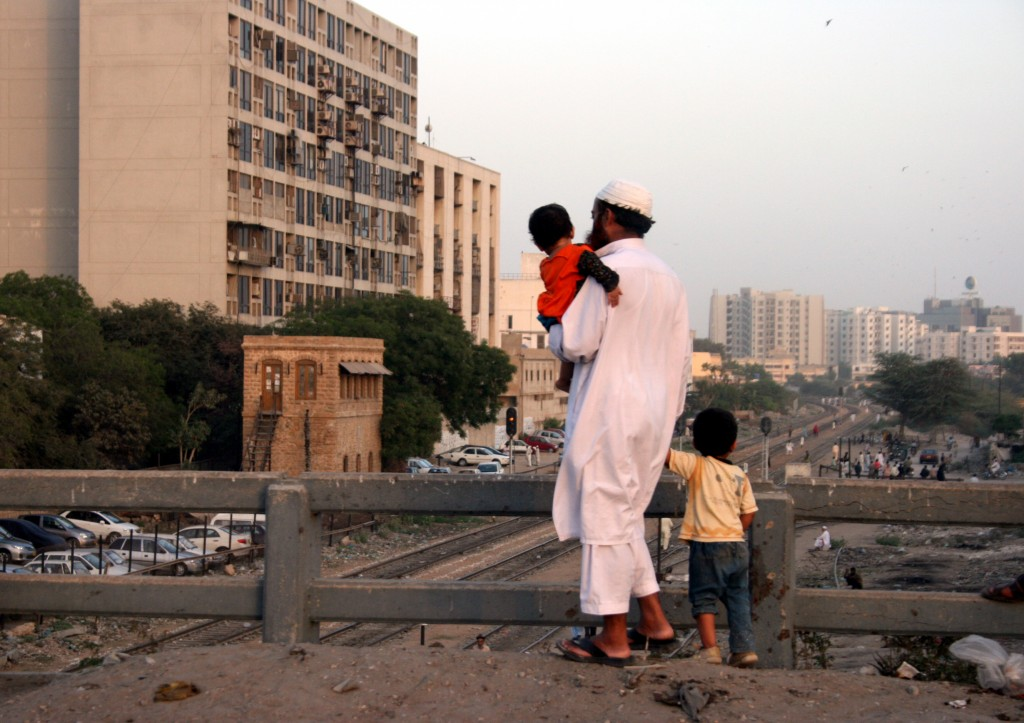 A man and his sons regard the city of Karachi in southern Pakistan. Photo by Larisa Epatko