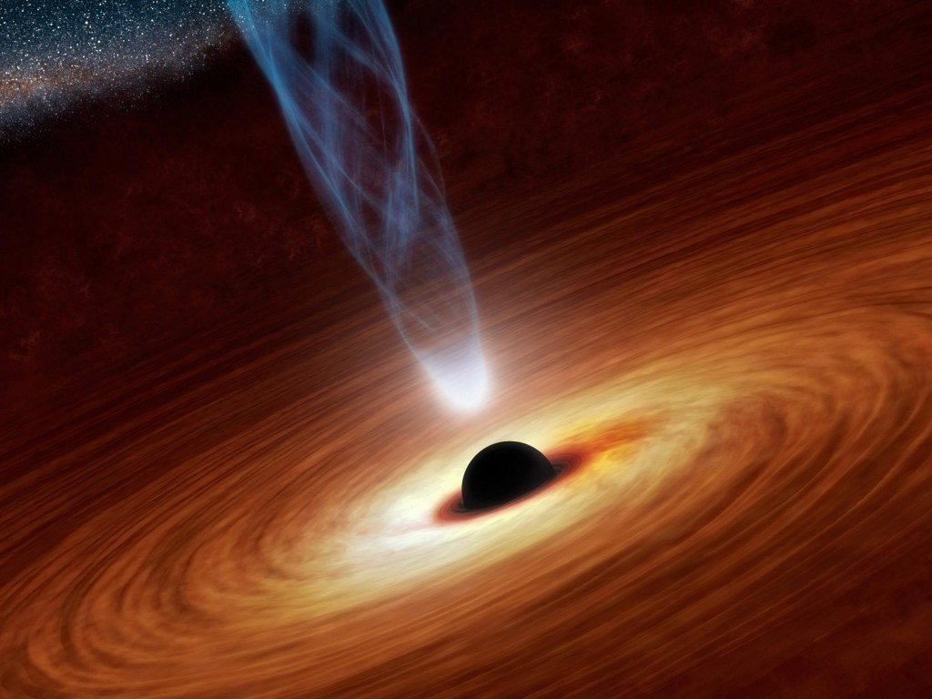 This artist's concept illustrates a supermassive black hole with millions to billions times the mass of our sun. Supermassive black holes are enormously dense objects buried at the hearts of galaxies. Image by NASA/JPL-Caltech