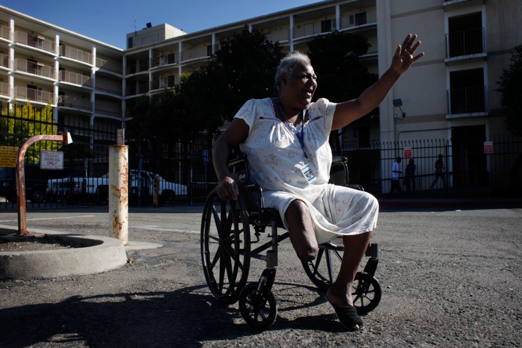 Rhonda Marshall, 58, waves to visitors outside the Hacienda public housing complex in Richmond, Calif. She's been living on the high-rise's first floor for years and has watched the building deteriorate. She says sees cracks in the walls running from the sixth floor to the ground and smells mold in the hallways and stairwells. Photo by Lacy Atkins/San Francisco Chronicle
