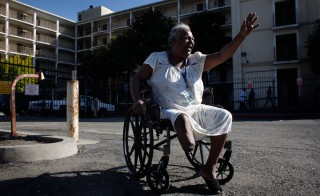 Rhonda Marshall, 58, waves to visitors outside the Hacienda public housing complex. She's been living on the high-rise's first floor for years and has watched the building deteriorate. She says sees cracks in the walls running from the sixth floor to the ground and smells mold in the hallways and stairwells. Photo by Lacy Atkins/San Francisco Chronicle