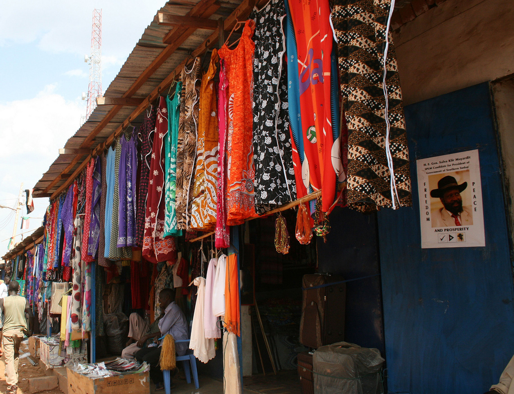 A stall selling clothes also displays a poster for Salva Kiir Mayardit, who is running for president of South Sudan. Photo by Larisa Epatko