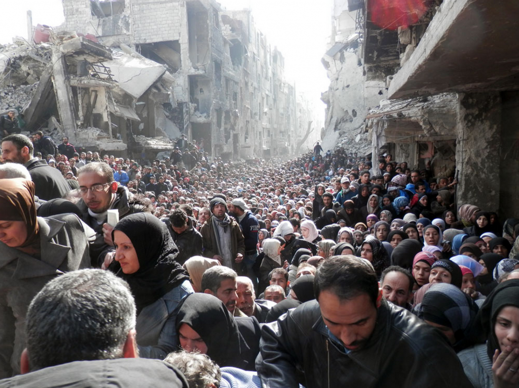 In this handout photo from the United Nation Relief and Works Agency, UNRWA, Yarmouk refugees in Syria gathered to wait for food aid in January 2014. Photo by UNRWA