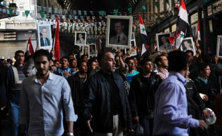 Syrian pro-government protesters hold pi