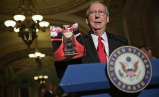 Sen. Mitch McConnell holds up a University of Louisville Cardinal's magazine during a Capitol Hill news conference in July 2013. Photo by Chip Somodevilla/Getty Images