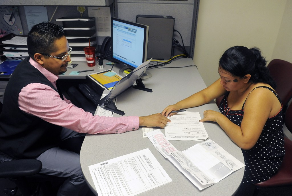 Enrollment Specialist Horacio Castaneda, left, helps Rosa Ayala Cruz, right, apply for health benefits at the Denver Health Westside Family Health Center on Oct. 1, 2013 in Denver. Photo by Chris Schneider/Getty Images