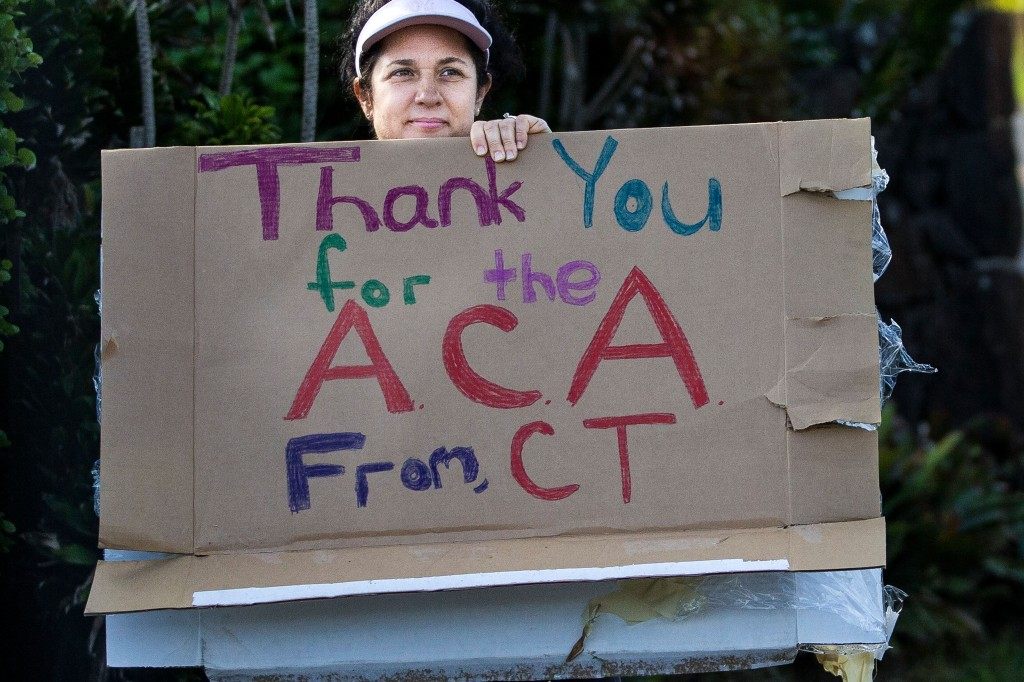 A woman holds a sign in support of the Affordable Care Act is seen as US President Barack Obama's motorcade in Hawaii in December 2013. Photo by Kent Nishimura/AFP/Getty Images