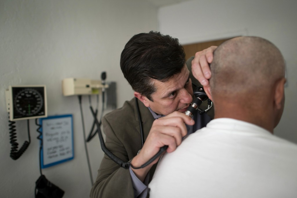 Esteban Lovato, a doctor at the La Loma Medical Center, does a routine check-up with a patient at the center's clinic in Oakland, California, U.S., on Friday, Jan. 31, 2014. Photographer: David Paul Morris/Bloomberg