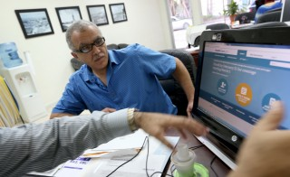 Hisham Uadadeh enrolls in a health insurance plan under the Affordable Care Act at Leading Insurance Agency in Miami, Florida. Photo by Joe Raedle/Getty Images
