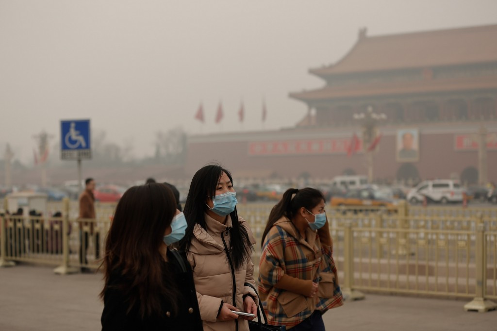 Beijing, like many other large Chinese cities, is often enveloped in heavy smog. Residents wear protective masks in February, 2014.  Photo by Getty images.