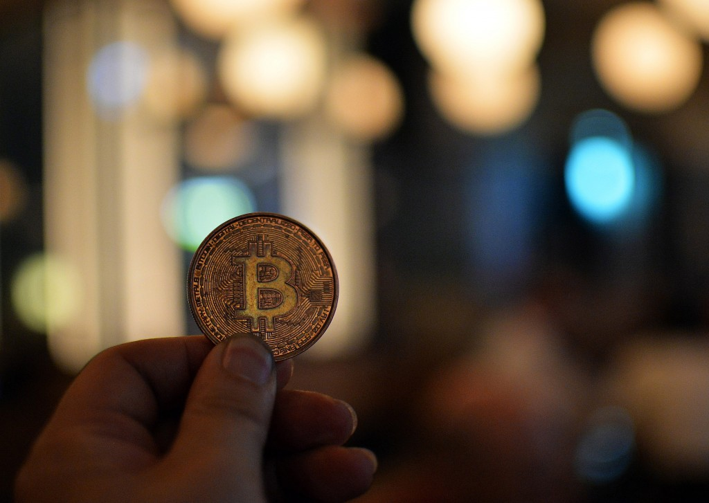 A man holds a bitcoin medal as members of bitcoin trading club hold a meeting in Tokyo on February 27, 2014. Bitcoin users in Tokyo gathered for a meeting set to be dominated by the shuttering of the MtGox exchange amid claims of a multi-million dollar theft.  AFP PHOTO / Yoshikazu TSUNO        (Photo credit should read YOSHIKAZU TSUNO/AFP/Getty Images)