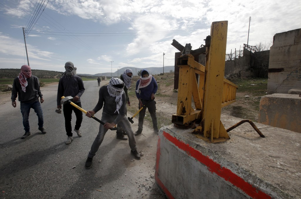 Palestinian activists try to destroy an Israeli checkpoint in the West Bank village of Bait Furik, east of Nablus, on March 1, 2014. Photo by Jaafar Ashtiyeh/AFP/Getty Images