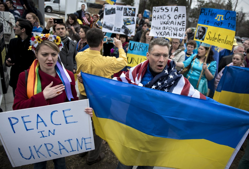 Protesters sing the Ukrainian national anthem near the Russian Embassy March 2, 2014 in Washington, DC. Activists gathered to protest Russian intervention in the Ukraine and Crimea. AFP PHOTO/Brendan SMIALOWSKI        (Photo credit should read BRENDAN SMIALOWSKI/AFP/Getty Images)