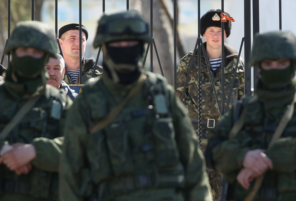 Ukrainian soldiers stand inside the gate of a Ukrainian military base as unidentified heavily-armed soldiers stand outside in Crimea Monday in Perevalne, Ukraine. Photo by Sean Gallup/Getty Images
