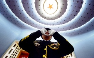 A Chinese People's Liberation Army, PLA, officer practices conducting the military band before the opening session of the 12th National People's Congress, NPC, in Beijing. The Chinese government annouced its 2014 budget Wednesday, including a 12.2 percent increase in defense spending. Wang Zhao/AFP/Getty Images
