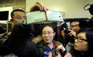 A woman holds up identification for a friend who may be aboard the missing Malaysia Airlines flight. Family and friends gathered in a Beijing hotel on Sunday awaiting news from the ongoing search off the coast of Vietnam.