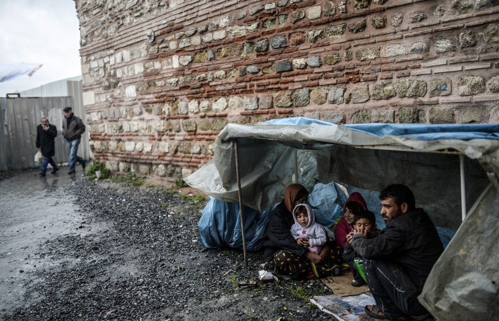 A Syrian refugee family from Aleppo seek shelter during a rainy day on March 8, 2014, in the Uskudar district of Istanbul, Turkey. Photo by Bulent Kilic/AFP/Getty Images
