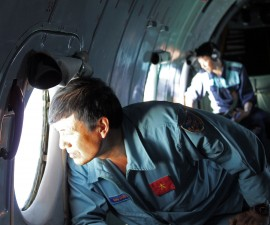 Military personnel on a Vietnamese aircraft scan the sea below for signs of