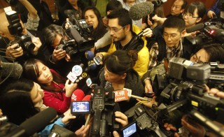 Media surround the relative of a passenger onboard Malaysia Airlines flight MH370 answers media questions at Lido Hotel on March 11, 2014 in Beijing, China. Photo by ChinaFotoPress/Getty Images