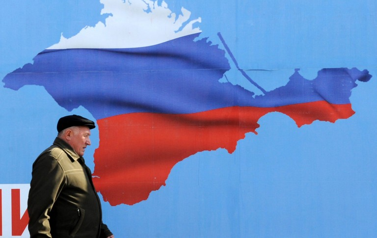 A man walks past a poster in Sevastopol in the Crimean Peninsula on March 11, 2014 depicting Crimea in the colors of the Russian flag. Photo by Viktor Drachev/AFP/Getty Images